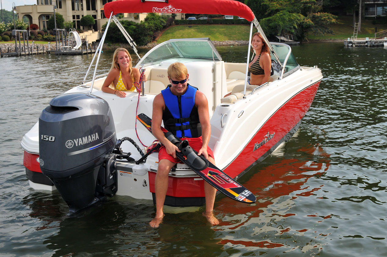 Man holding water ski on back of NauticStar 223DC Boat