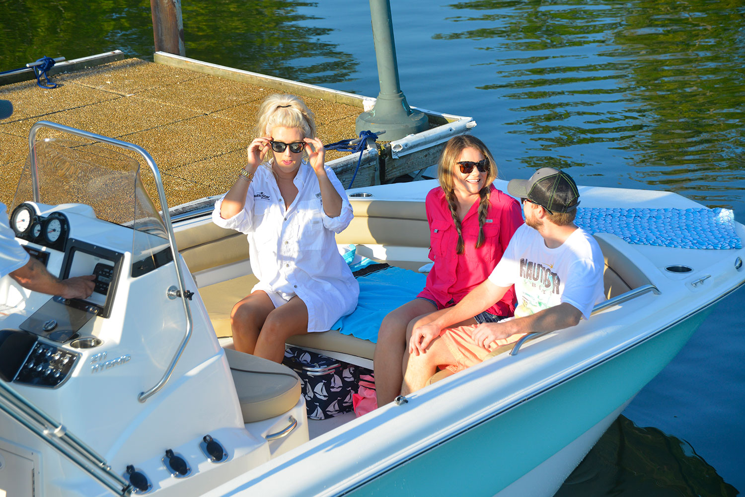 One man and woman talking while another woman relaxes on the NauticStar 211 Hybrid
