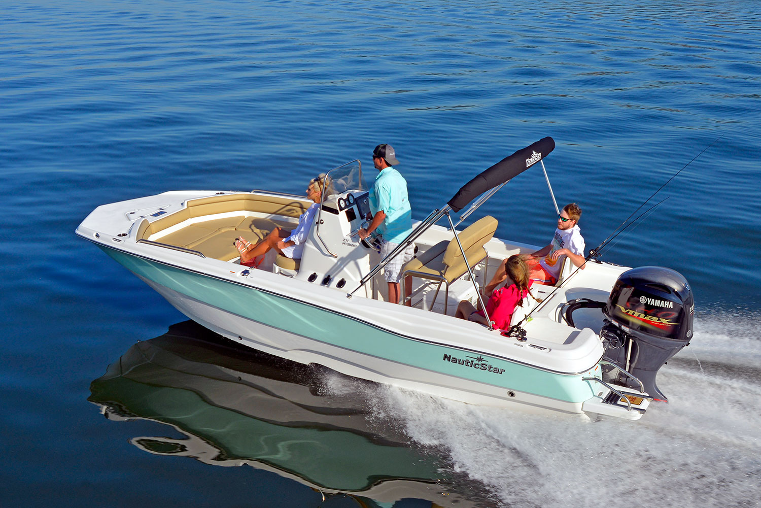Two women and a man lounge while another man captains the NauticStar 211 Hybrid