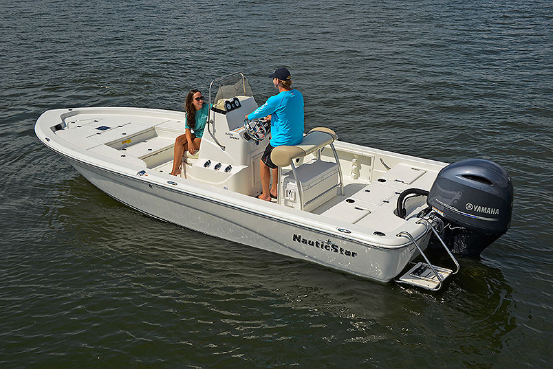 Man captaining the NauticStar 2200 Sport while chatting with a woman