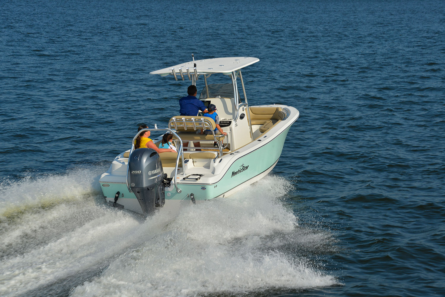 Man captaining the NauticStar 2303 Legacy with a woman, girl, and boy on board