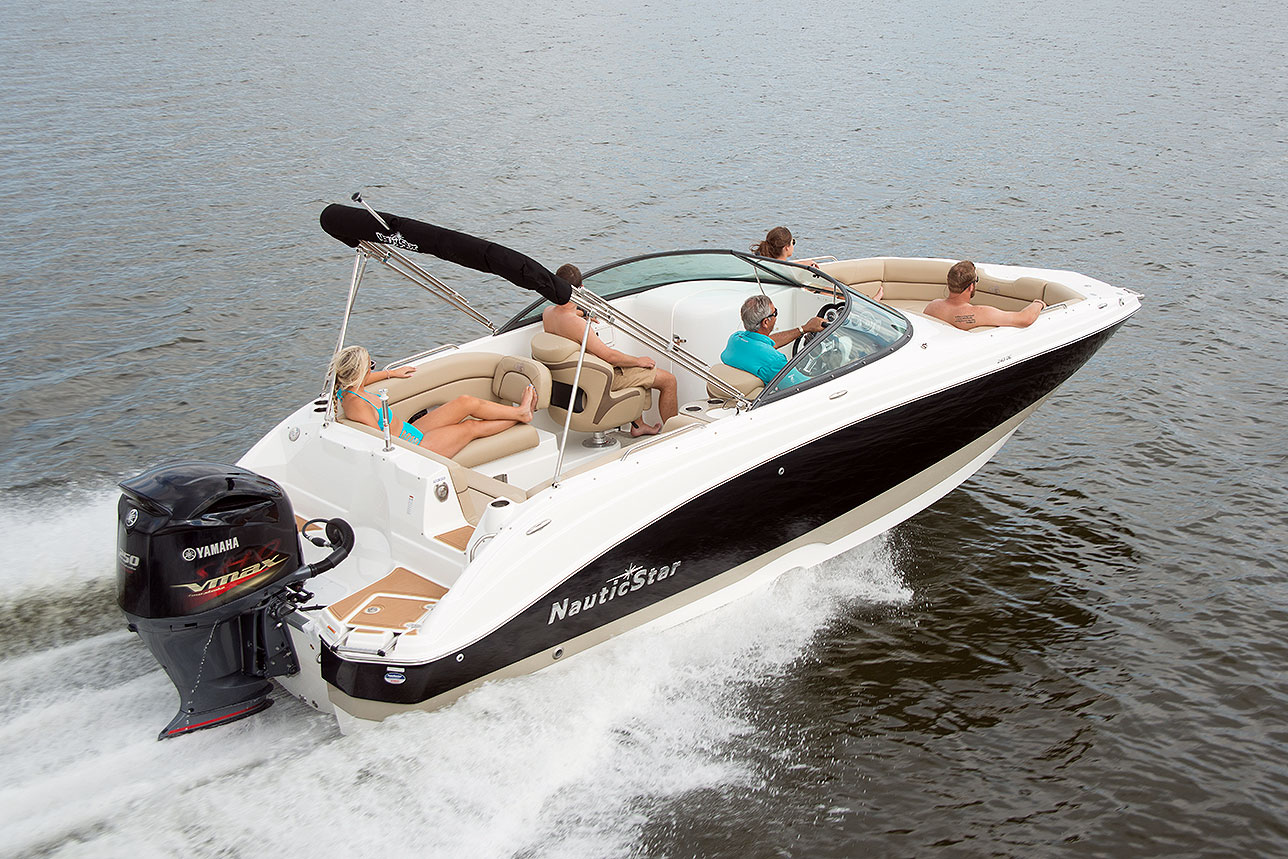 A man captaining the NauticStar 243 DC while two men and women lounge