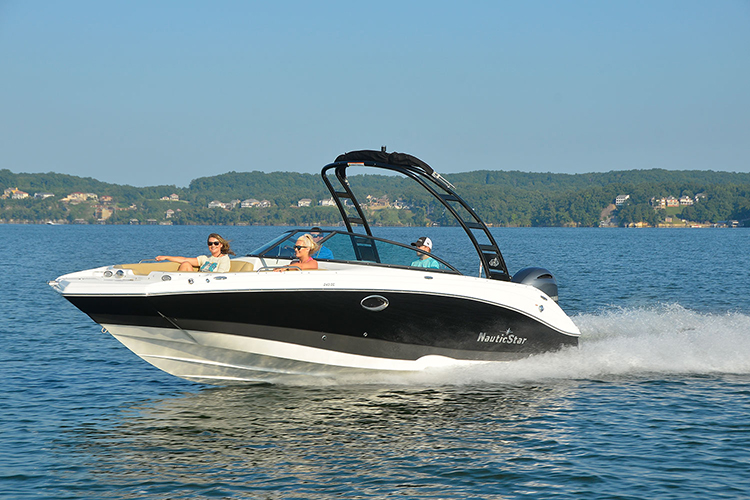 Two men running a NauticStar 243 DC with two women lounging