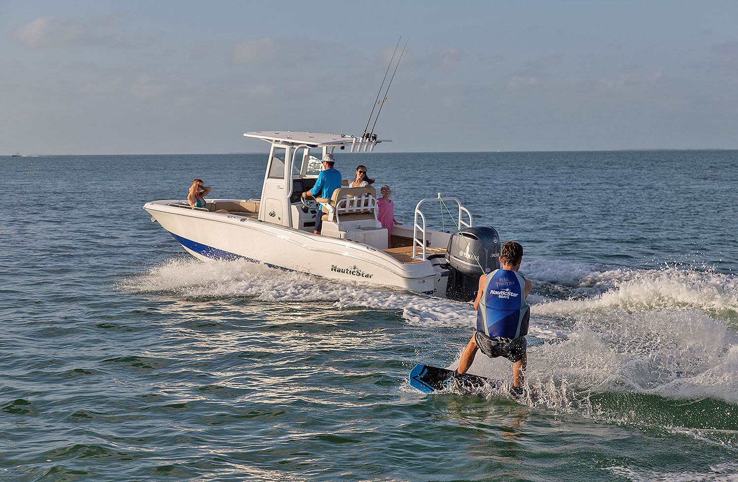 Man waterskiing while two women and a girl watch on a NauticStar 251 Hybrid