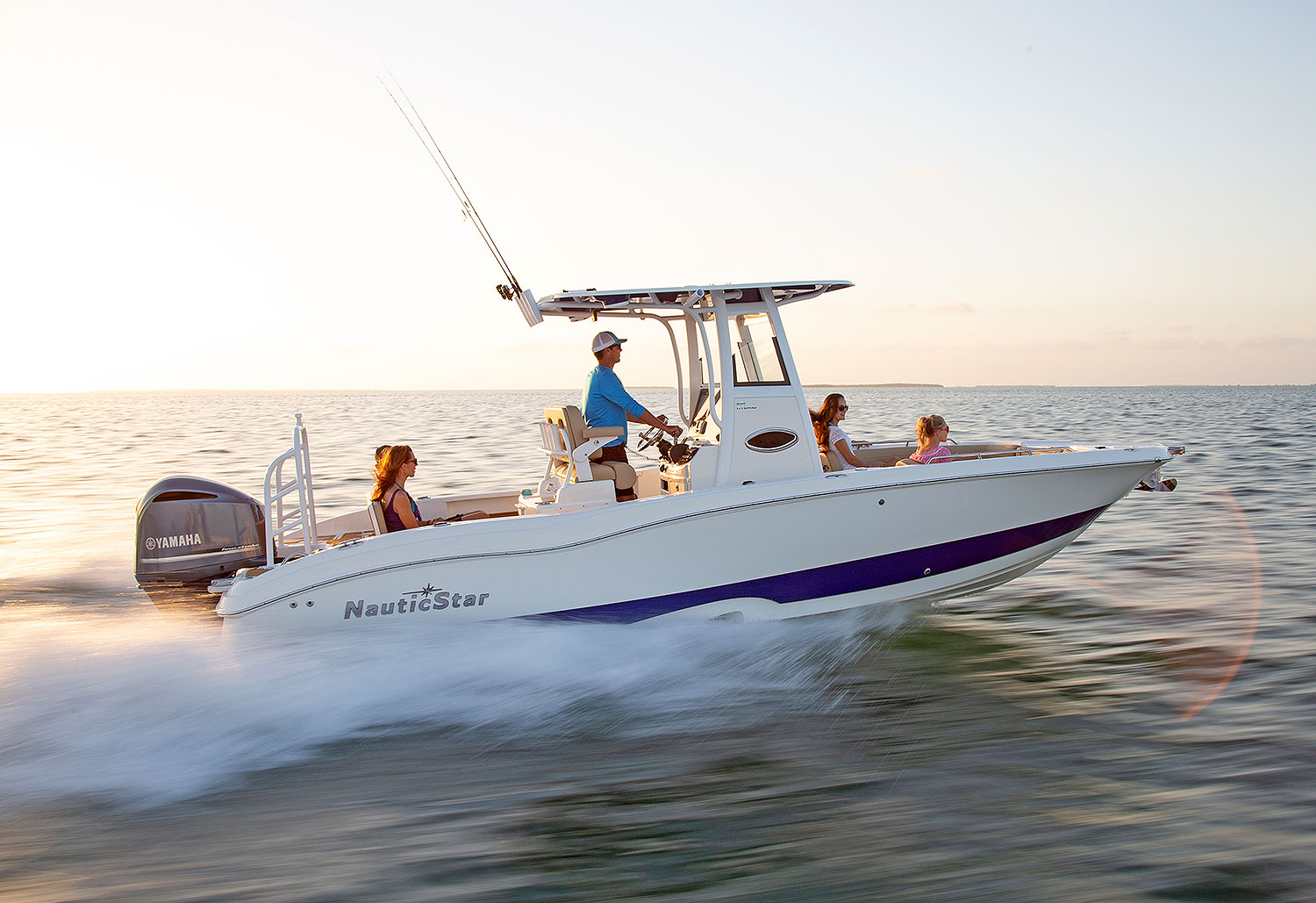 Three women and one man speeding on a NauticStar 251 Hybrid boat
