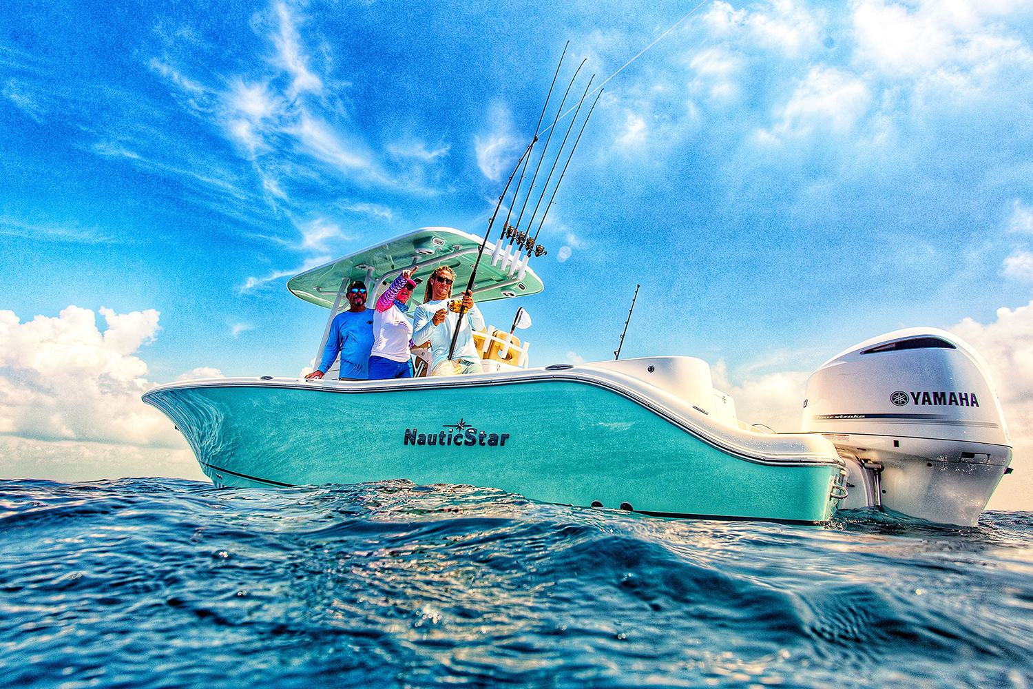 Man fishing on a NauticStar 28 XS with a woman pointing out to sea and a man watching