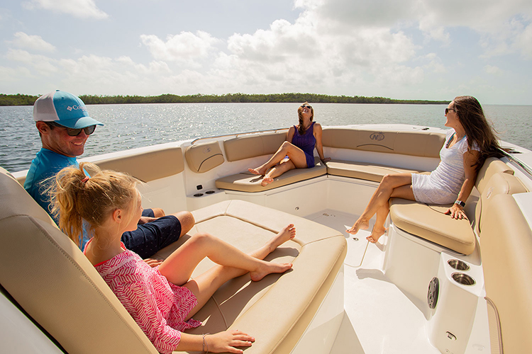 Two women, one girl, and one man lounging on a NauticStar 32 XS