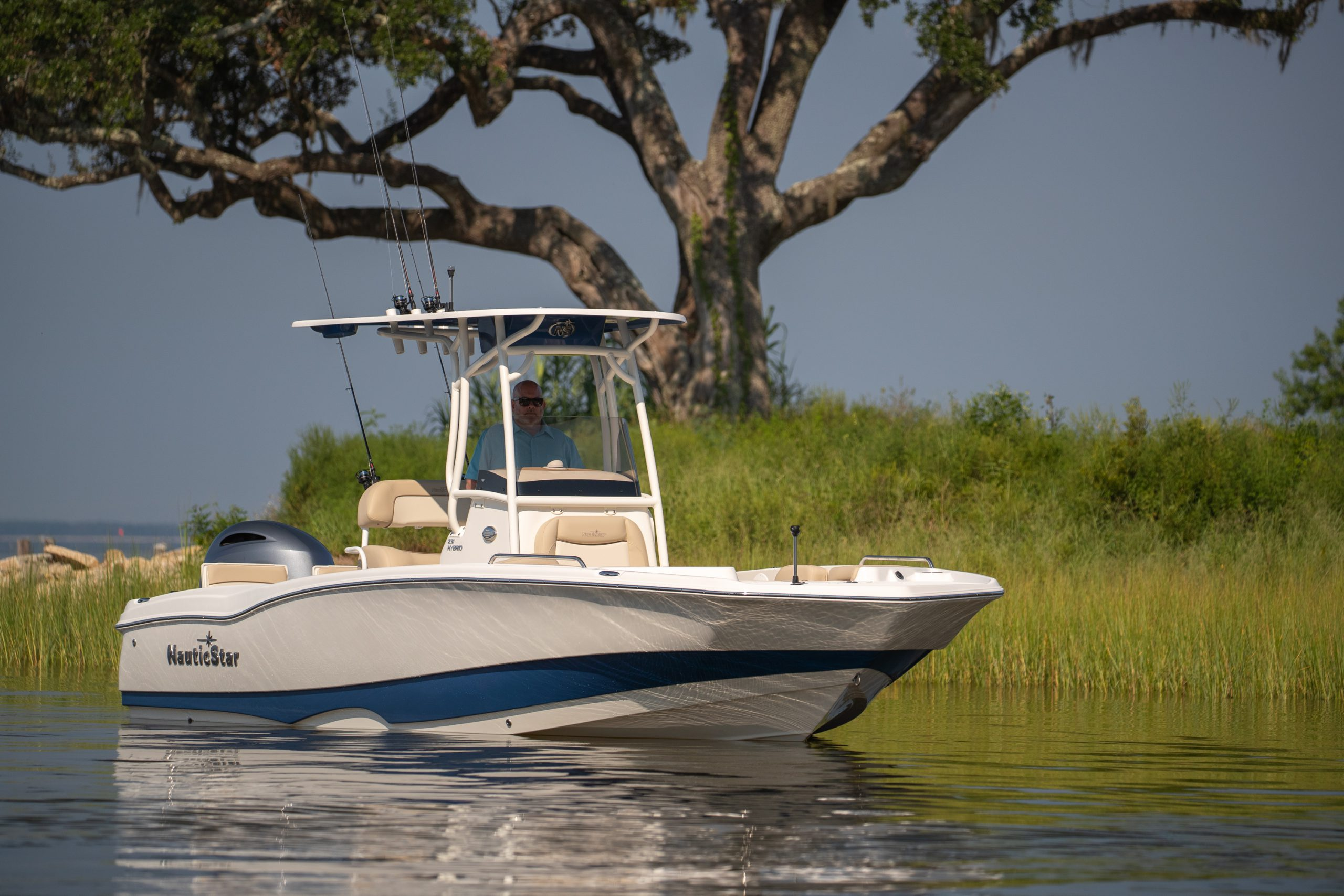 A NauticStar 231 Hybrid boat floats in a beautiful grassy bay bayou