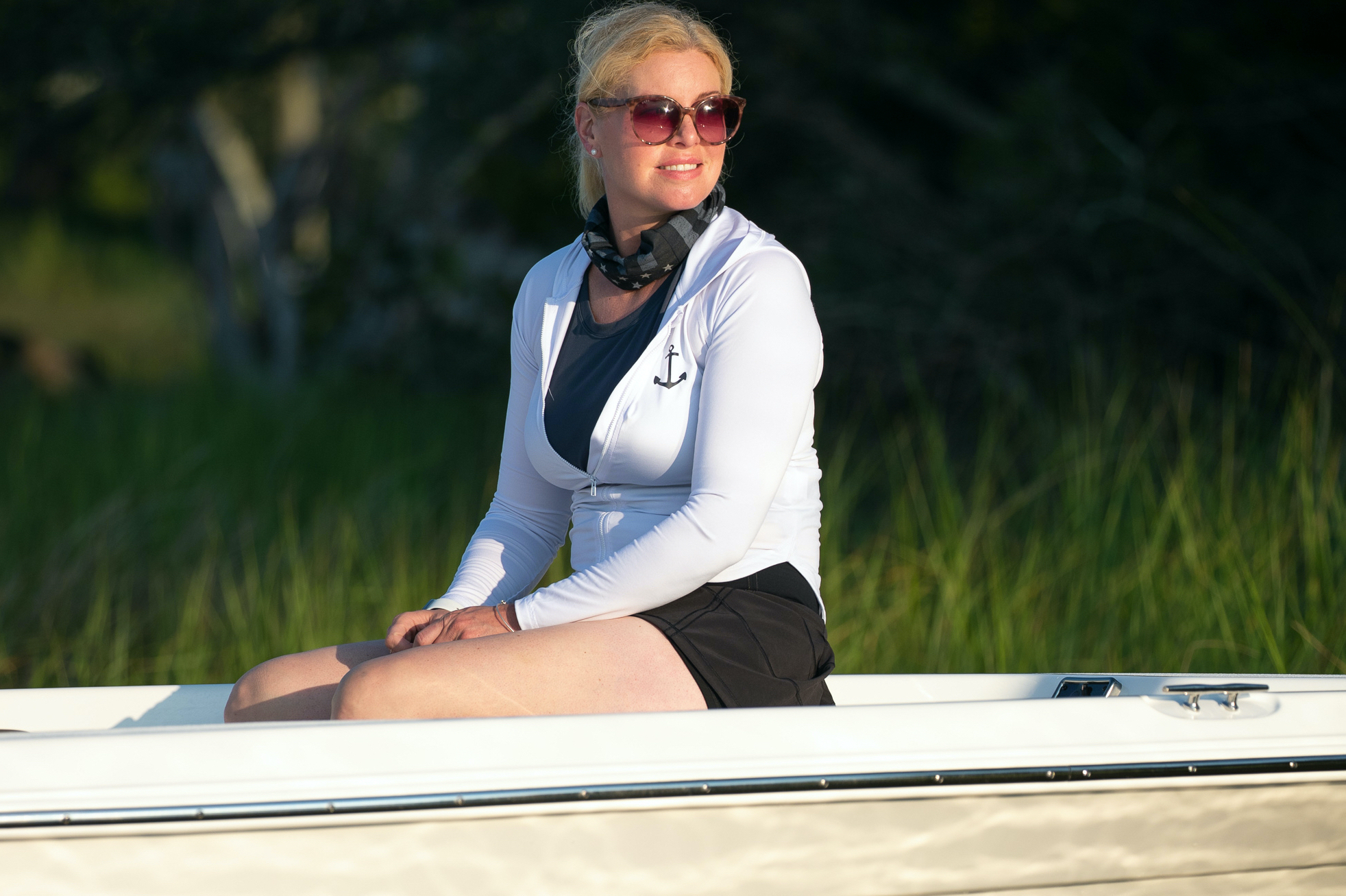 A woman sits on the casting deck of a NauticStar 215SB boat
