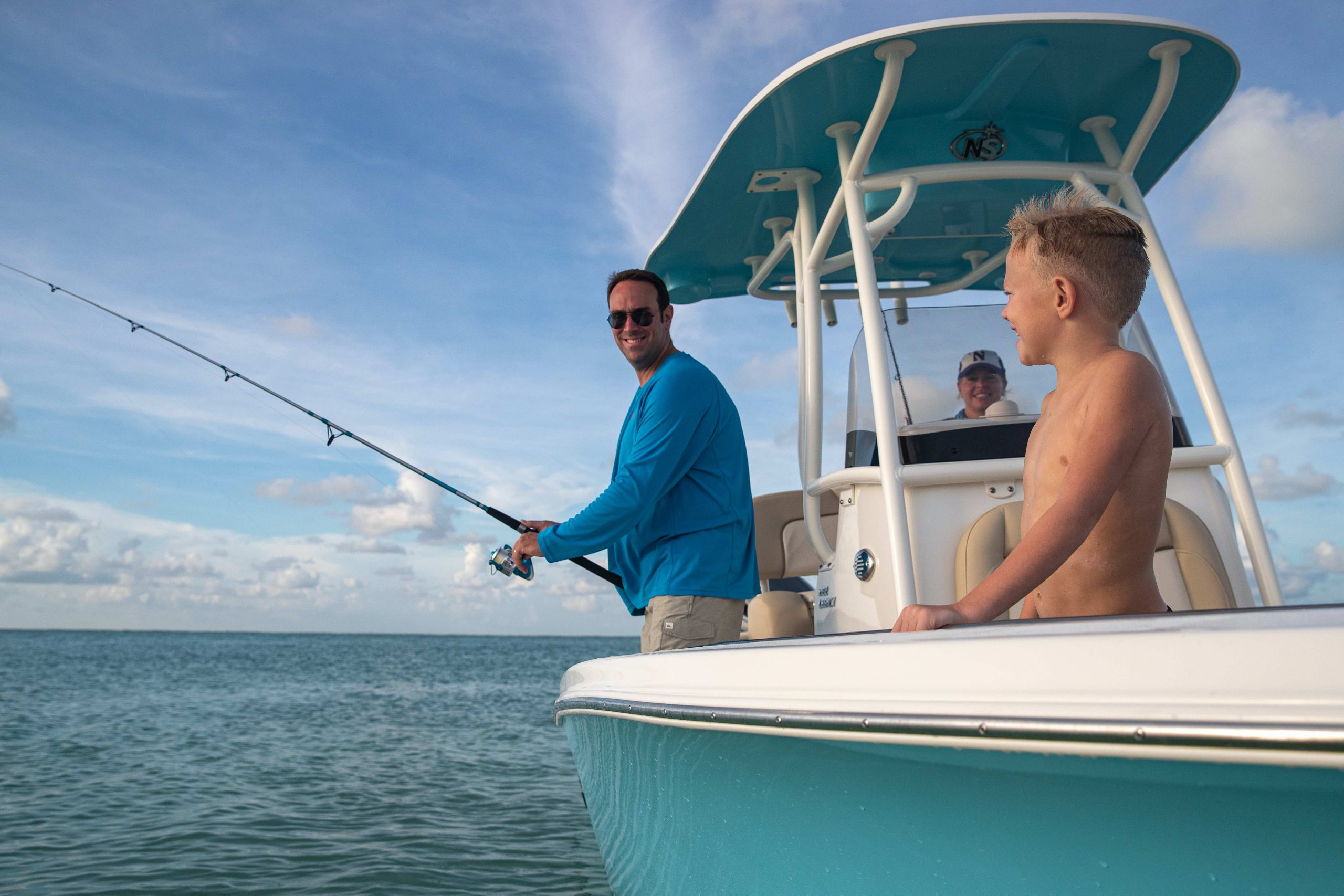 Dad and Son fish on the starboard side of a 2021 Carolina Blue NauticStar 2102 Legacy