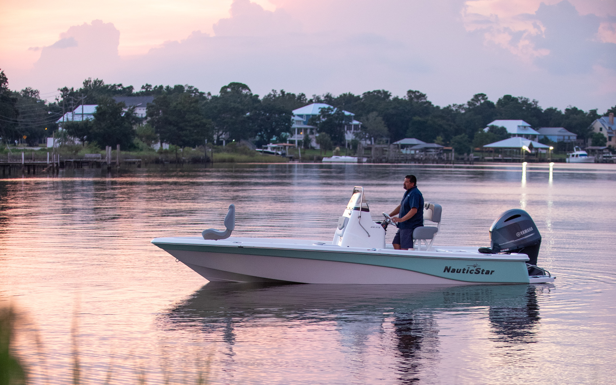 A captain sits at the helm of a NauticStar 215XTS boat in calm waters at dawn.