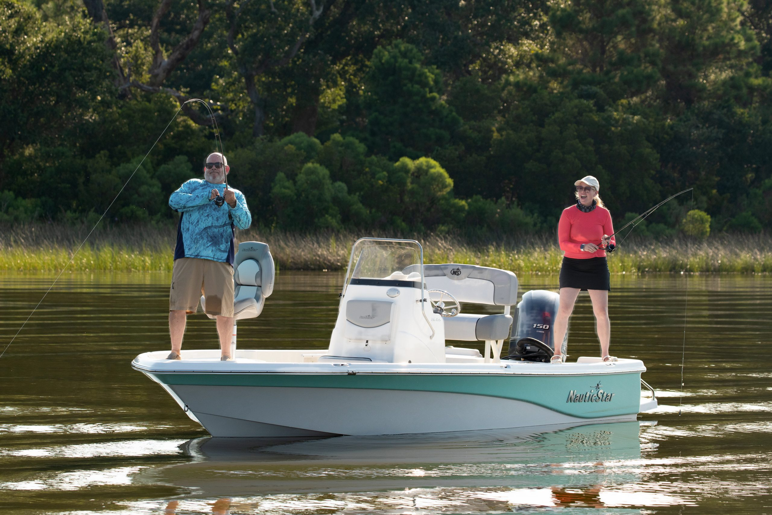 A man reels in a big catch from the casting deck of a NauticStar 215XTS boat while a woman watches from the transom