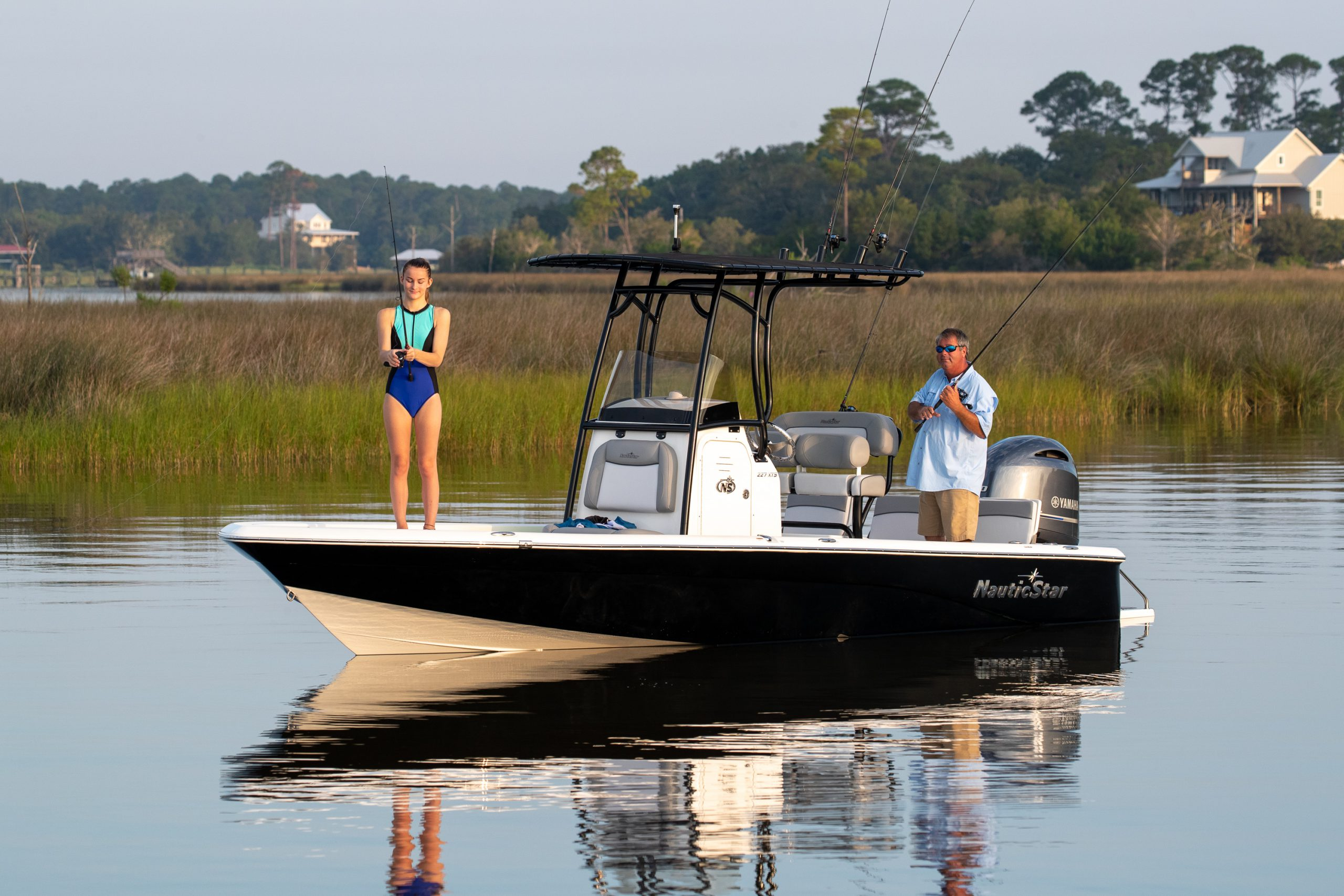 A girl fishes from the deck of a NauticStar 227 XTS center console boat